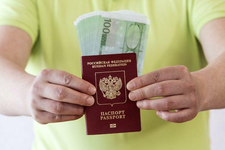 паспорт и деньги в руках мужчины