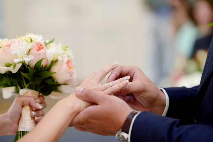 мужчина одевает обручальное кольцо женщине