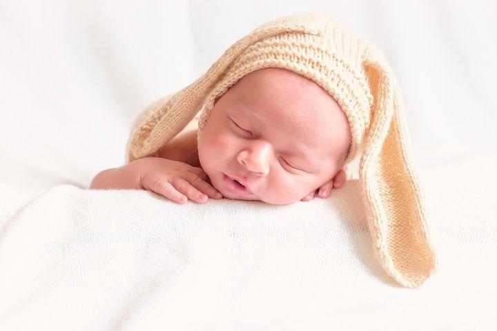 Новорожденный мальчик в шапке с ушками