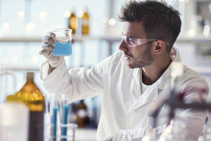 мужчина химик смешивает вещество
