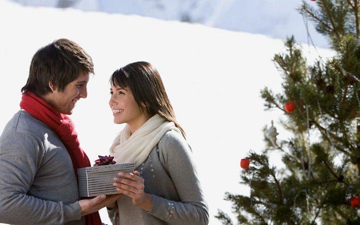 мужчина вручает новогодний подарок женщине