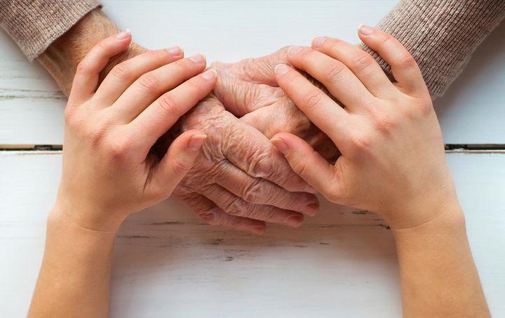 Пожилая и молодая женщина держатся за руки