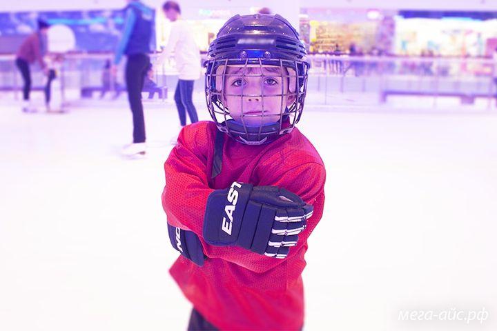 Мальчик играет в хоккей на катке